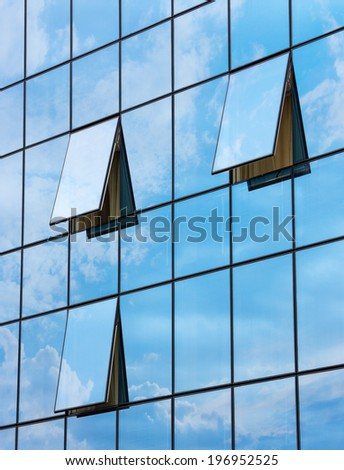 wall glass skyscraper with reflection of the sky and the three open windows  - stock photo