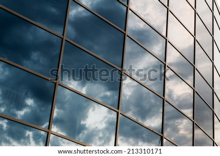 wall glass skyscraper with reflection of the sky at night. - stock photo