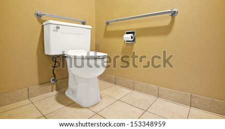 Wall handles help the disabled and handicap use the toilet with easier access. - stock photo