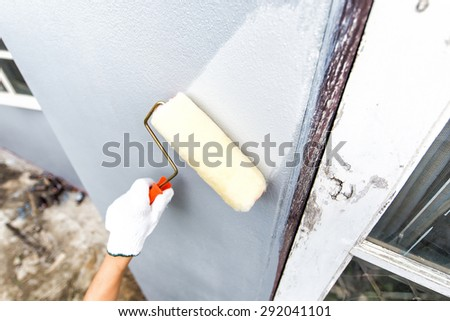 wall in a new building as a background and paint roller in a working position. - stock photo