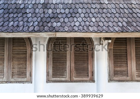 Wall in cafe with wooden shutters windows under tile roof - stock photo