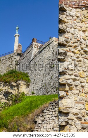Wall Kalemegdan fortress and a monument Victor in the distance. - stock photo