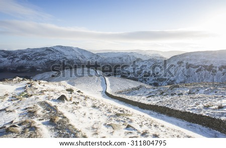 wall leading to the mountains covered in winter snow and ice, helvellyn, cumbria - stock photo