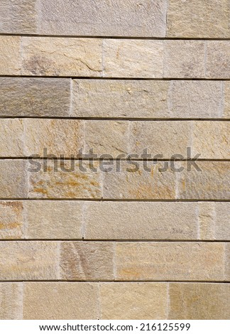 Wall lined with colorful gneiss slabs in sunny day