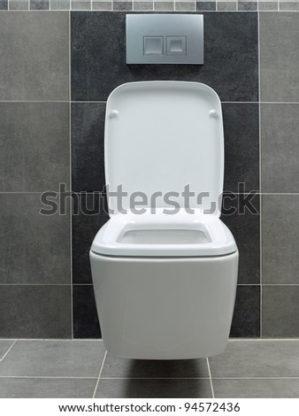 Wall mounted white ceramic toilet in gray tiled bathroom - stock photo