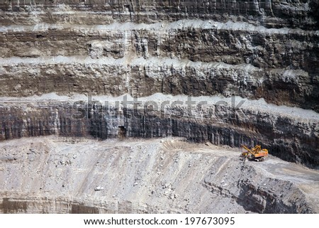 Wall of a modern diamond mine in the north of Russia and a big yellow machinery, Sakha Yakutia, Udachny town  - stock photo