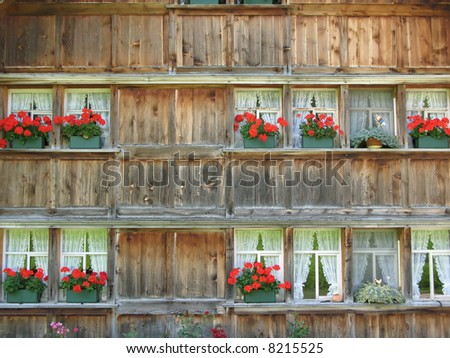 Wall of a traditional Swiss wooden house with flower pots - stock photo
