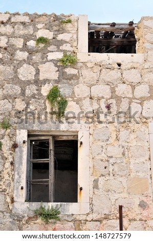 Wall of abandoned, damaged, old house with two windows