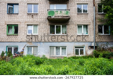 Wall of an old apartment building and abandoned garden - stock photo