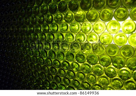 Wall of back-lit green bottles