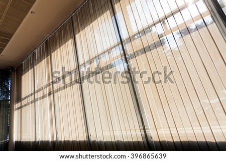 Wall of glass covered with white curtains