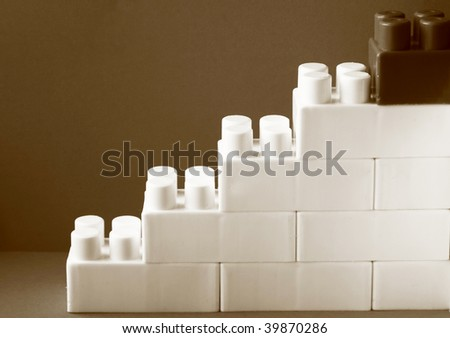 wall of lego and steps on grey background - black and white. - stock photo