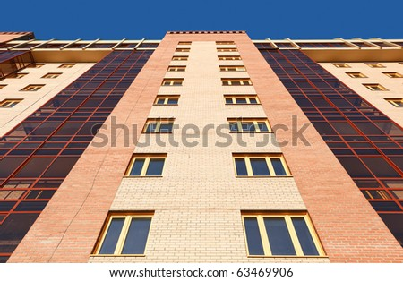 Wall of modern apartment house against a blue sky.