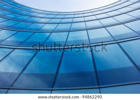 wall of modern building with reflection of sky and clouds - stock photo