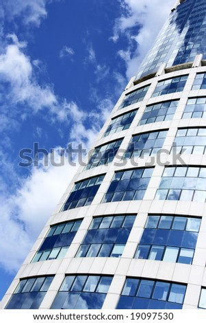 Wall of office building and sky reflction in the windows - stock photo