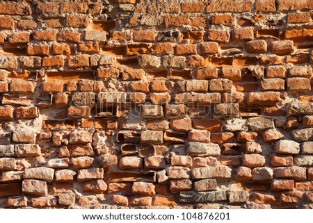 Wall of the old damaged bricks. - stock photo