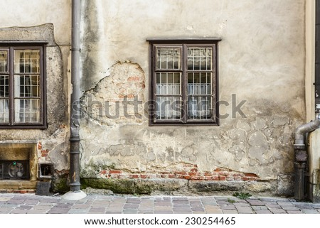 Wall on European city street with windows and crumbling plaster. - stock photo