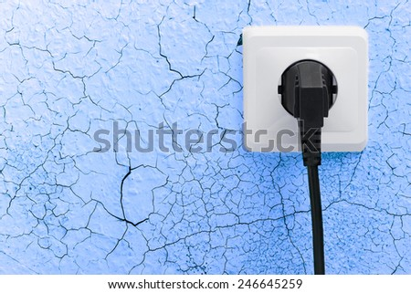 Wall plug socket on cracked colored wall background