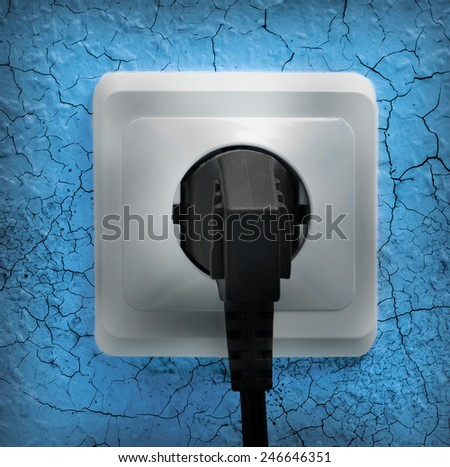Wall plug socket on cracked colored wall background - stock photo