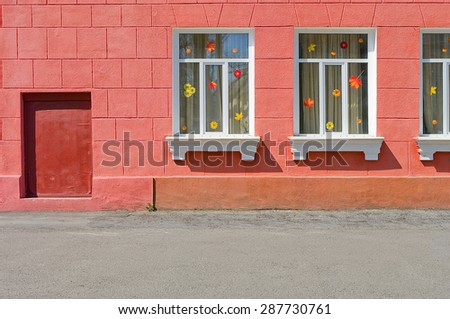 wall red facade of the house building with windows on a city street