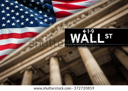 Wall Street sign with American flag on the background. - stock photo