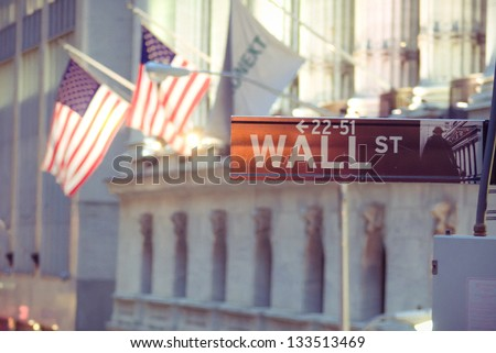 Wall Street sign with American flags and New York stock exchange in the background. - stock photo
