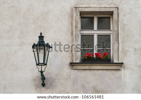 wall with a lamp and a window with flowers - stock photo