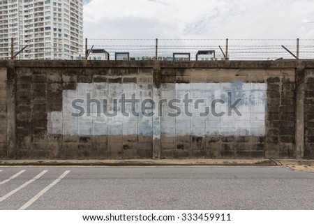 Wall with barbed wire fence - stock photo