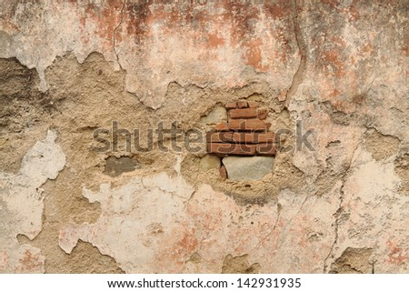 Wall with broken plaster and visible bricks - stock photo