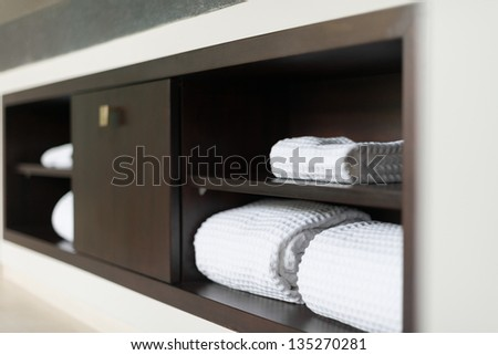 Wall with built in wooden shelf. Neat stack of white soft towels in bathroom. Closet with clean folded textile for spa and hygiene. Modern interior of hotel room. Luxury resort with classic design. - stock photo