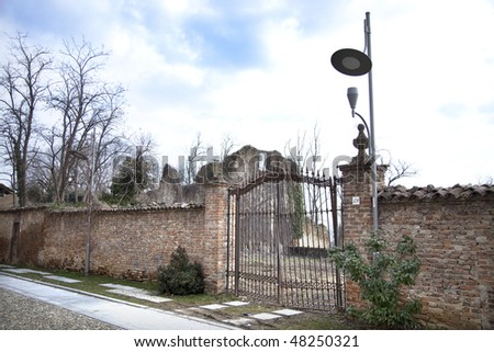 Wall with closed gate, ancient ruins, dead trees and streetlight. - stock photo
