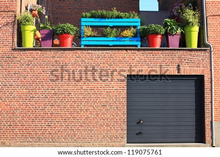 Wall with garage and brightly coloured flower pots - stock photo