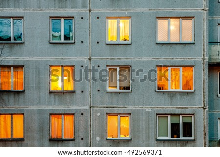 Wall with iIluminated windows. Detail of soviet era block apartment building