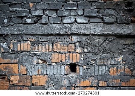 Wall with old bricks and partially covered in soot - stock photo