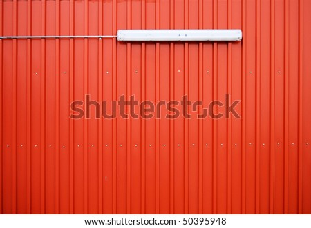 Wall with orange cladding and a lamp - stock photo