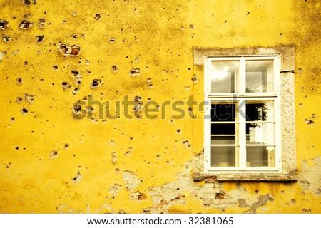 Wall with shrapnel holes - stock photo
