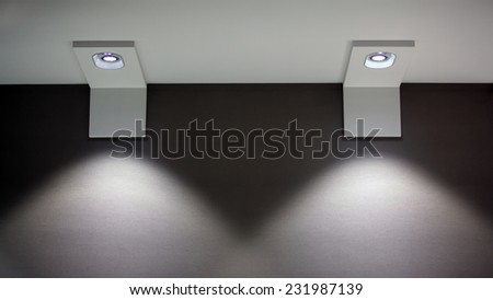 Wall with two lamps that shine down. Selective focus. - stock photo