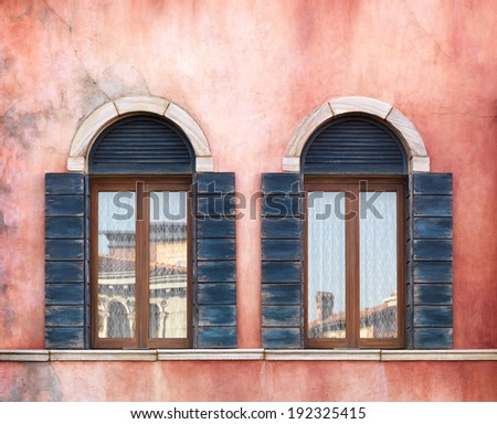 Wall with two old arched windows with shutters, rustic texture - stock photo