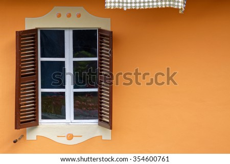 Wall with two shutters and window in orange wall - stock photo
