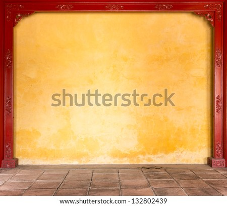 Wall with yellow stucco framed with decoration. Grungy wall with golden floral pattern on dark brown wooden boards both sides. Abstract background. Building exterior or interior. - stock photo