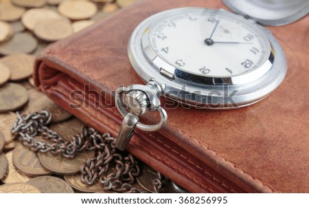 Wallet and pocket watch on the coins background - stock photo