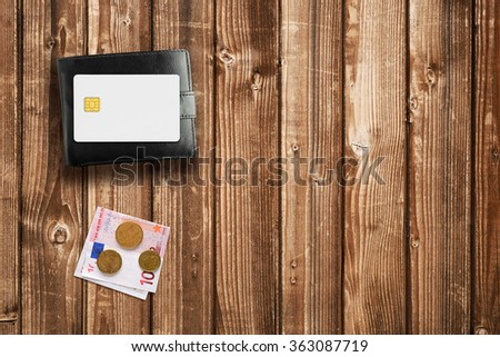 Wallet, money and credit card on wooden table top view