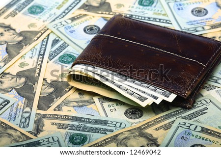 Wallet with couple of $100 dollar bills over a bed of $100 and $20 dollar bills