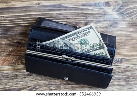 Wallet with dollars. Black leather purse with money lying on the wooden background. - stock photo