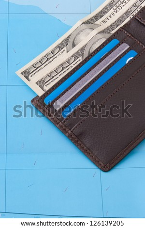 Wallet with dollars cash and credit cards on map background for travel concept. - stock photo