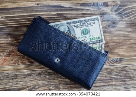Wallet with dollars,  flat lay. Black leather purse with money lying on the wooden background.