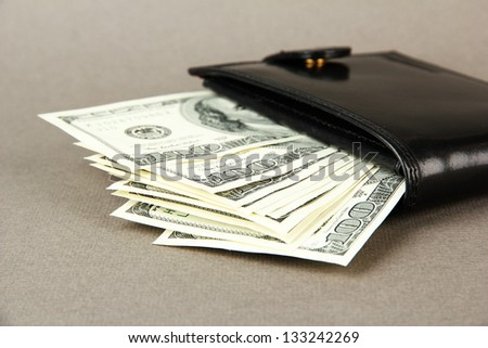 Wallet with hundred dollar banknotes, on color background