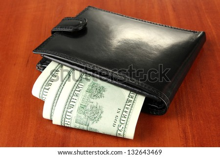 Wallet with hundred dollar banknotes, on wooden background