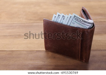 Wallet with money on wooden background. Closeup