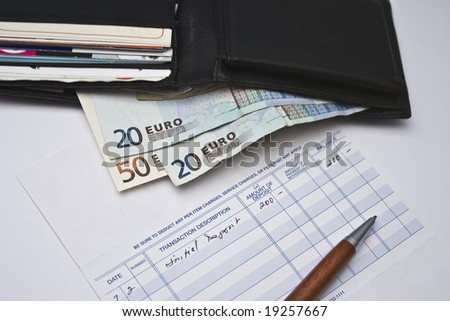 wallet with money, pay check and pen
